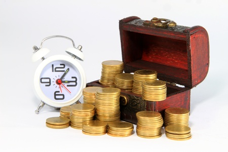 Gold alarm clock lay on money in a wooden chest Stock Photo - 14062277