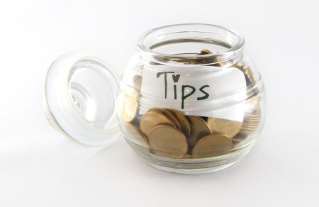 Glass bank for tips with money isolated on white Stock Photo - 14290611