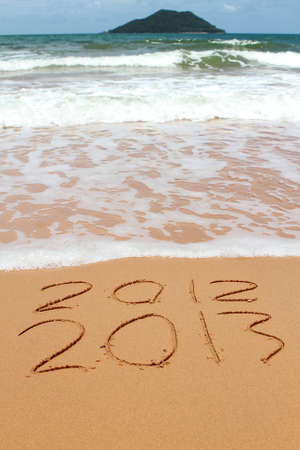 2013 year on the sand beach near the ocean. 2012 is been erasing by wave Stock Photo - 14470310