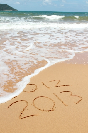 2013 year on the sand beach near the ocean. 2012 is been erasing by wave Stock Photo - 14470308