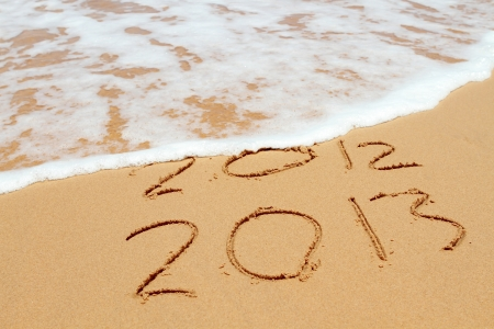 2013 year on the sand beach near the ocean. 2012 is been erasing by wave Stock Photo - 14470305