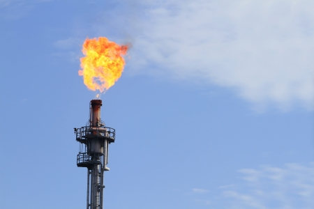 Burning oil flare on a blue sky photo