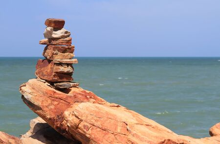 Pebble stone pyramid against blue sea photo