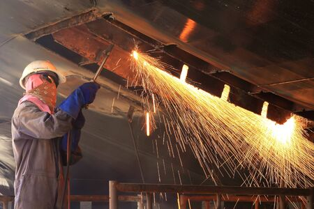 a welder working a torch at shipyard photo