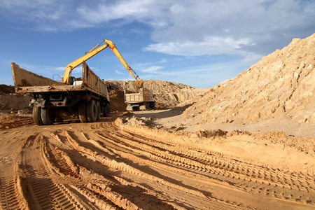 Heavy excavator loading dumper truck with sand in quarry over blue sky photo