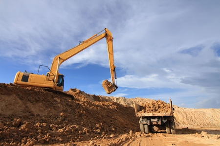 sand quarry: Heavy excavator loading dumper truck with sand in quarry over blue sky Stock Photo