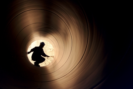 A silhouette of a worker in pipe Stock Photo