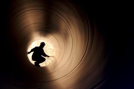 A silhouette of a worker in pipe Standard-Bild