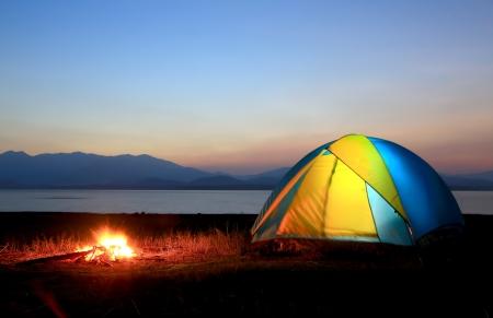 テント、キャンプファイヤー日没で、湖のほとりに