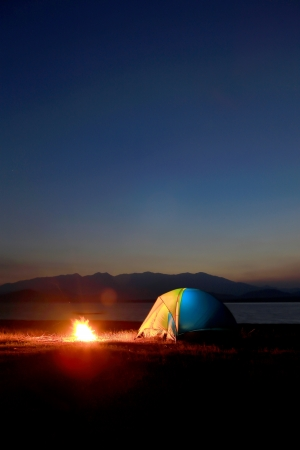 tent and campfire at sunset,beside the lake photo