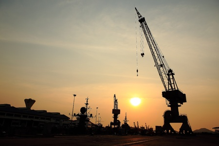 dockside: Cranes in dockside at sunset Stock Photo