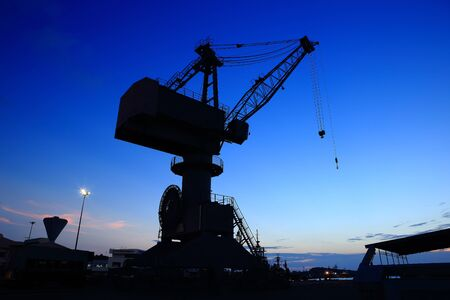 Cranes in dockyard  at sunset photo