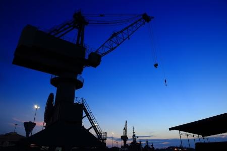 Cranes in dockyard  at sunset photo