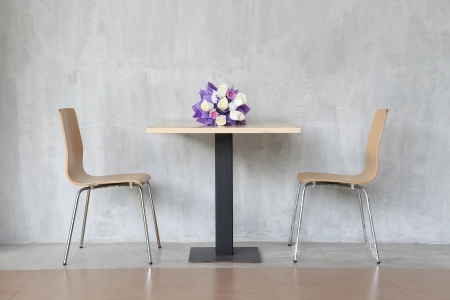 modern interior table and two chairs with flowers. photo