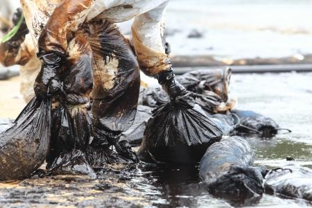 contaminacion ambiental: limpiar la mancha de crudo en el Ao Prao Beach en, Rayong, Tailandia