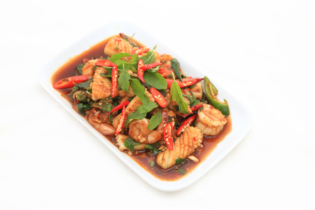 Spicy seafood fried served on white dish photo