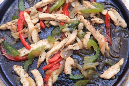 skillet: Hot skillet of chicken fajitas and vegetables