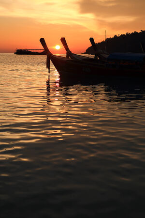long tail boats at sunset at Koh Lipe in Satun, Thailand photo