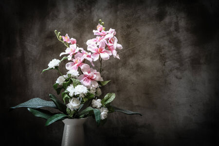 Bouquet of peonies in a vase against  wall. Interior with retro filter effect photo