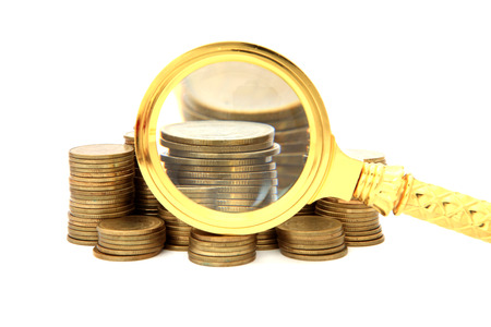 Magnifier and gold coins. On a white background. photo