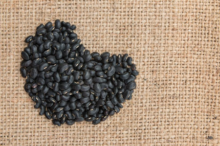 turtle bean: Heart shape made up of black beans on sack background.