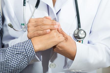 Medical doctor holding senior patient's hands Standard-Bild