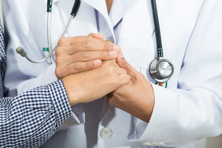 Medical doctor holding senior patients hands