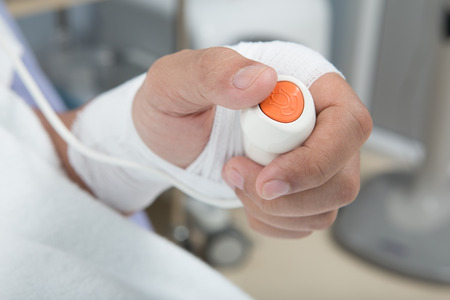 nursing sister: Hand pressing emergency nurse call button Stock Photo