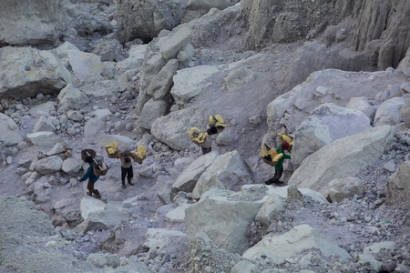 steep cliffs: KAWAH IJEN, INDONESIA - OCT 12: Worker carries a basket with pieces of sulfur on his shoulder on October 12, 2015.. Miners each carry up to 90kg of sulfur up steep cliffs at Kawah Ijen volcano.