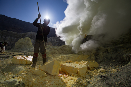 gaseous: KAWAH IJEN, INDONESIA - OCT 12: Worker at sulfur mine inside Ijen crater on October 12, 2015. Miners are extracting gaseous sulfur going out in the mine of the crater Editorial