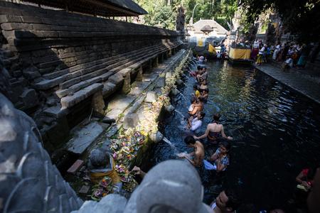 recite: BALI ,INDONESIA - OCTOBER 10, 2015 : Travellers praying and take a bath at holy spring water at Tirta Empul Hindu Temple Bali ,Indonesia. Editorial