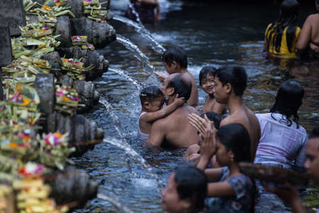 almighty: BALI ,INDONESIA - OCTOBER 10, 2015 : Travellers praying and take a bath at holy spring water at Tirta Empul Hindu Temple Bali ,Indonesia. Editorial