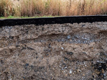 Close to rocky and sandy soils under paved roads