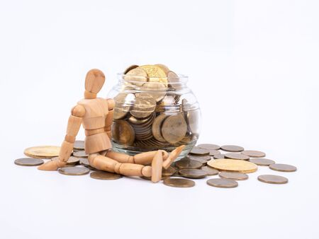 Miniature wooden figure sits on spilled jar with coins. Business concept with coins