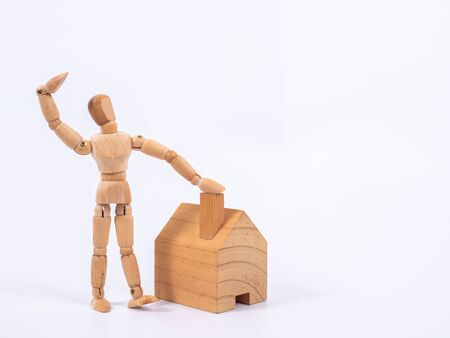 L'homme s'appuya contre le modèle d'une maison isolée sur fond blanc. Concept avec une marionnette en bois. Banque d'images