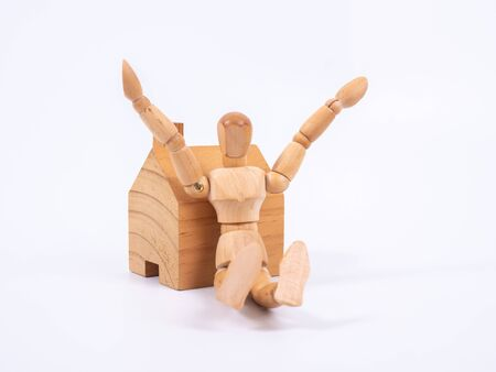 Man leaned against the model of a house isolated on white background. Concept with a wooden puppet.