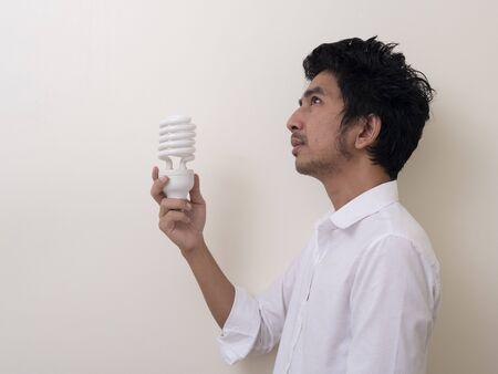 Man holding energy saving bulb for lamp Standard-Bild - 147038764