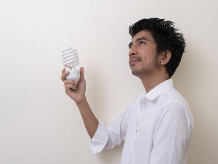 Man holding energy saving bulb for lamp Standard-Bild - 147038770