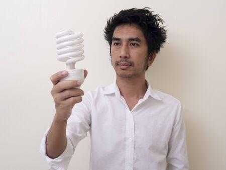 Man holding energy saving bulb for lamp Standard-Bild - 147038772