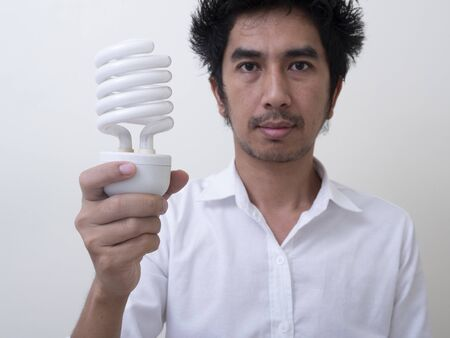 Man holding energy saving bulb for lamp Standard-Bild - 147038742