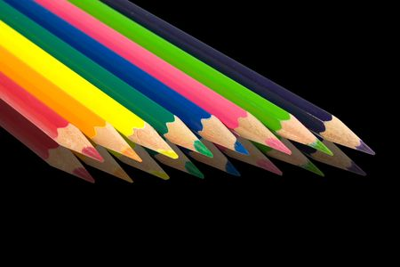 Assortment of coloured pencils with shadow on black background