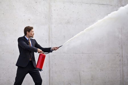 quench: Businessman using fire extinguisher at a target as if controlling damage og problems Stock Photo