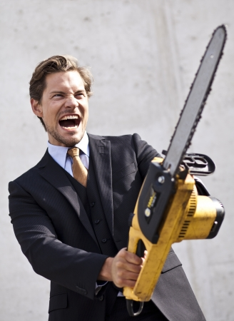 assured: Businessman holding chainsaw high prepared for battle or problems ahead