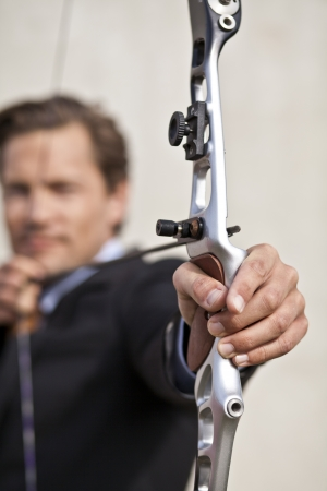 fixate: Confident businessman targeting something in the distance with his bow and arrow
