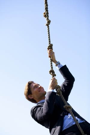 pursue: Businessman climbing a rope  Concept of achievement, hard work and challenges