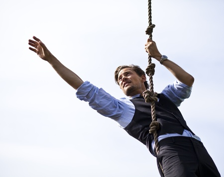 pursue: Focused businessman hanging from a rope, reaching ambitiously towards the future Stock Photo