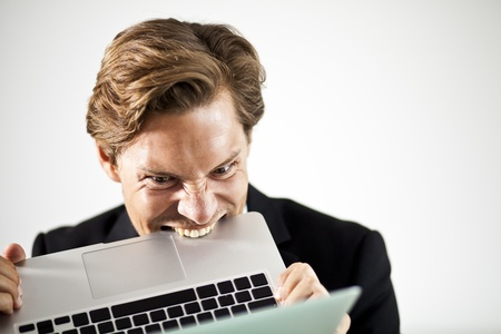 bothered: Man biting a laptop in frustration