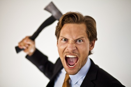 cutting costs: Caucasian businessman with a axe cutting costs or giving someone the axe.