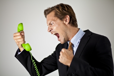 Businessman screaming at phone photo