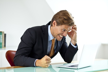 breakdown: Frustrated Businessman Sitting At Desk In Office Using Laptop With Hand To His Head  Stock Photo